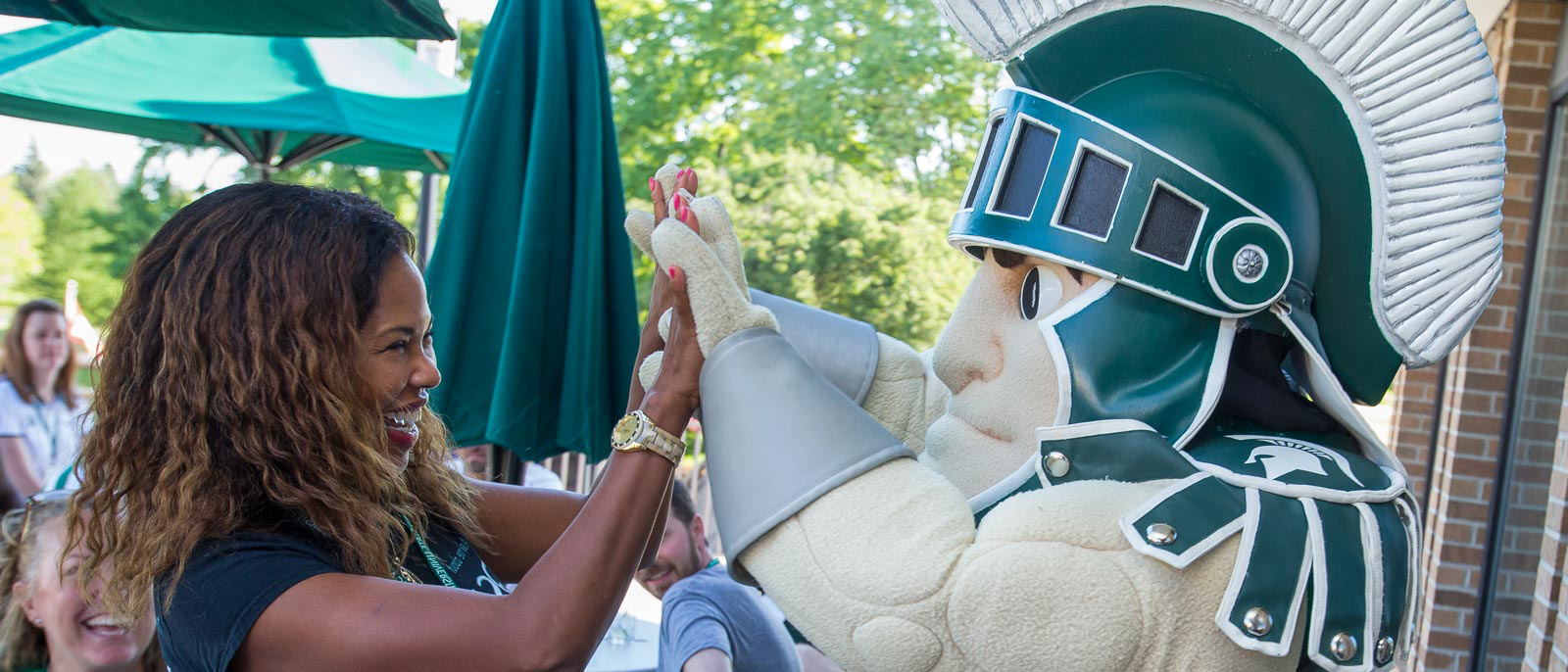 Woman high fives Sparty in an outdoor patio setting on a sunny day outside the Henry Center