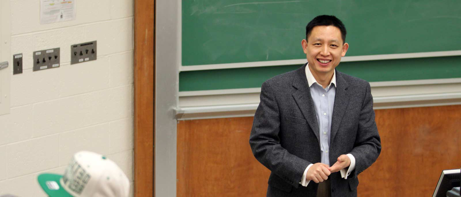 AIS faculty members Xuefeng Jiang smiles as he stands at front of classroom, during an accounting course at MSU.