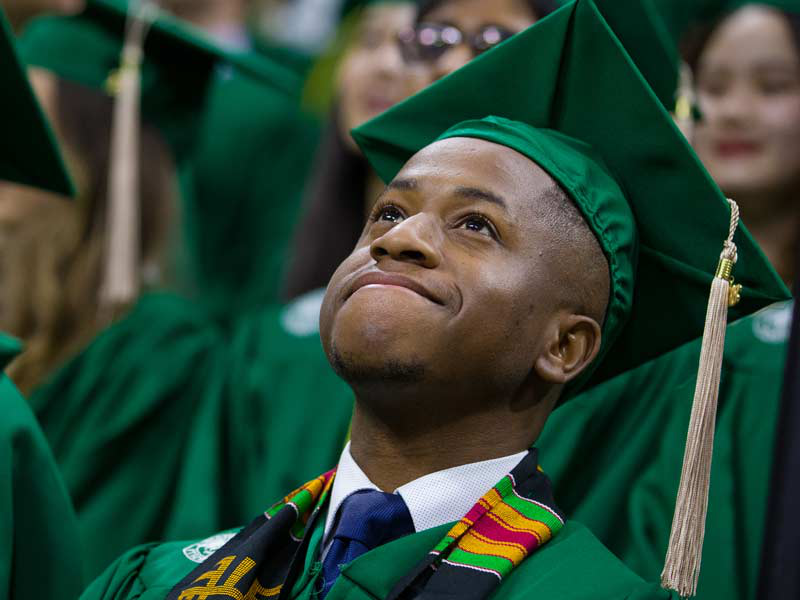 Graduating business school student at MSU looks up, hopeful, at undergraduate commencement ceremony.